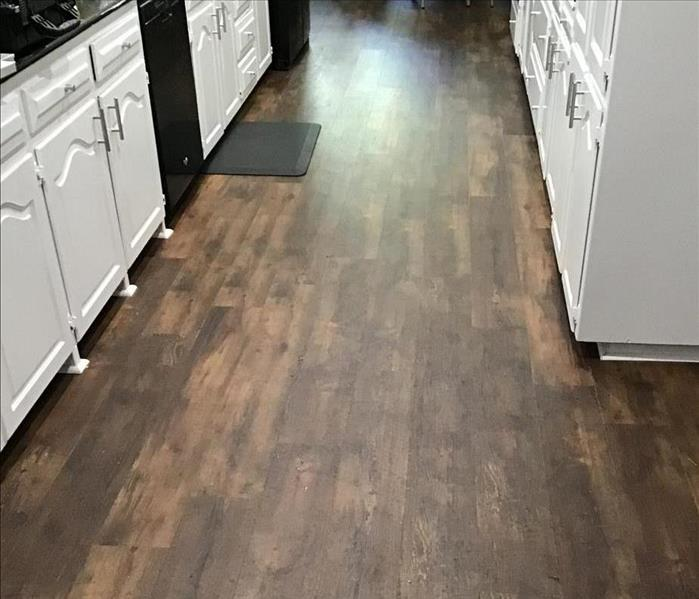 wooden floor in a kitchen with white cabinets