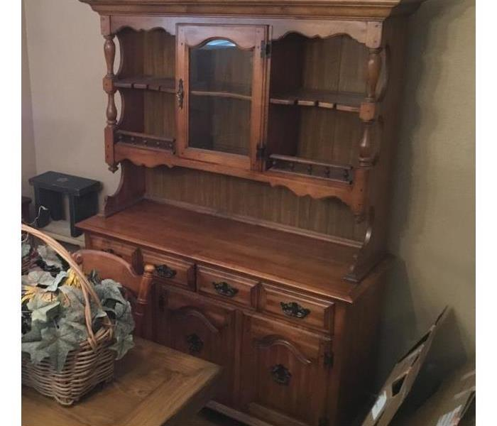 a wooden china cabinet with empty shelves