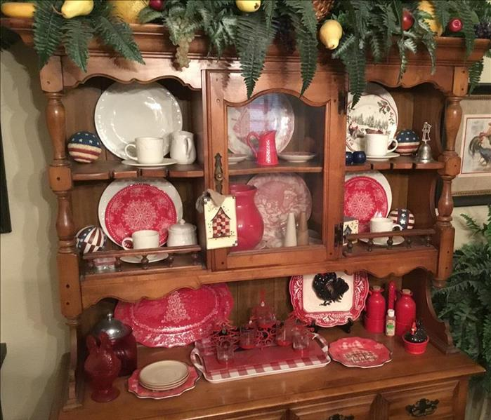 a wooden china cabinet with dishes and decor