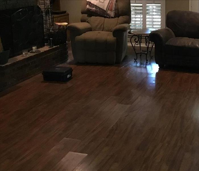 Living room with a fireplace and damaged wood flooring