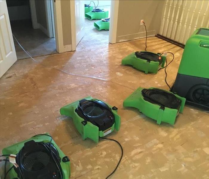 a bare floor with several green drying machines in a bedroom