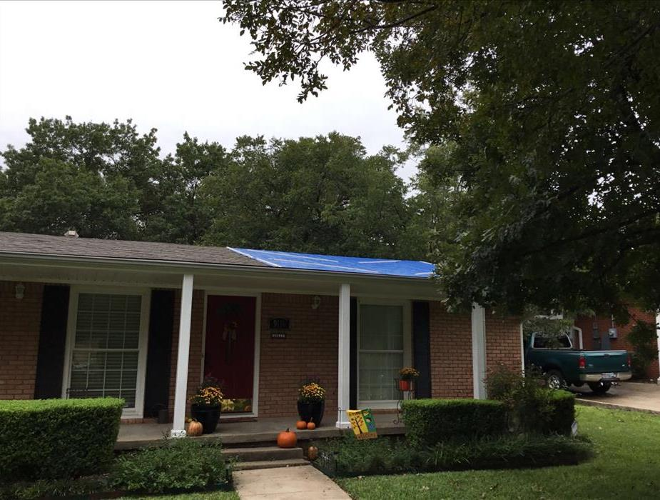 a blue tarp covers a portion of a roof on a home