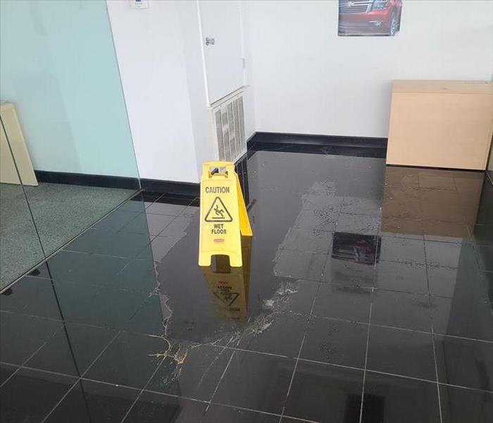 A puddle of water on a dark tiled floor and yellow slip hazard signs