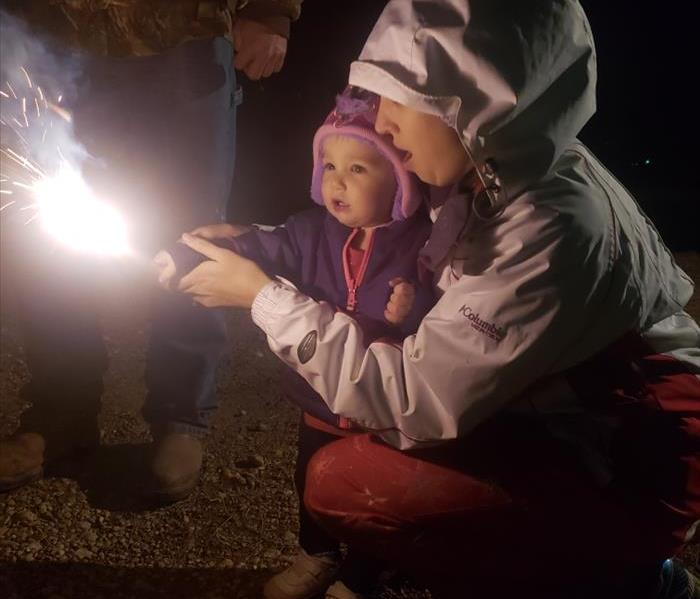 Mother helping her toddler hold a lit sparkler