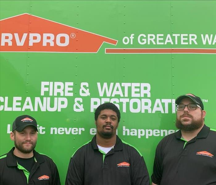SERVPRO production crew in front of a company SERVPRO green production vehicle