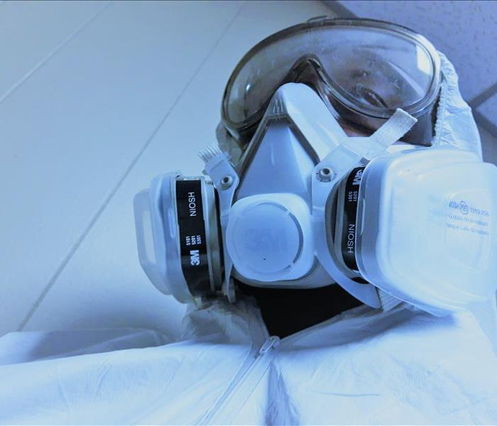A man in a white protective suit, goggles, respirator and green latex gloves