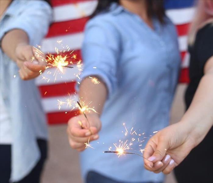 three women hold lit sparklers in their hand away from their bodies