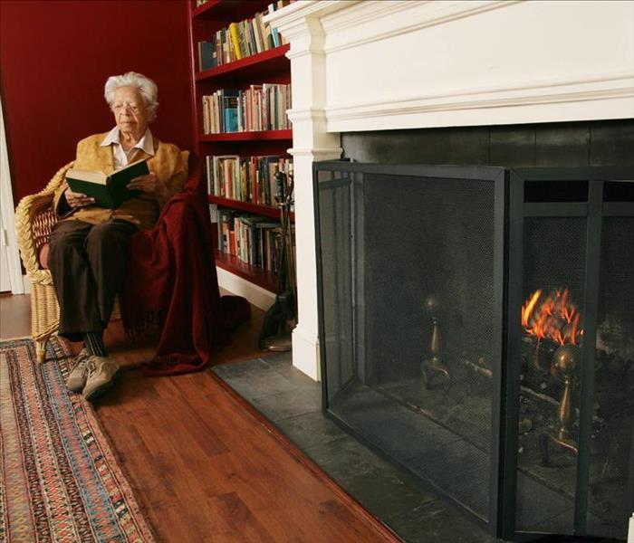 Older adult woman reading by a screened fireplace