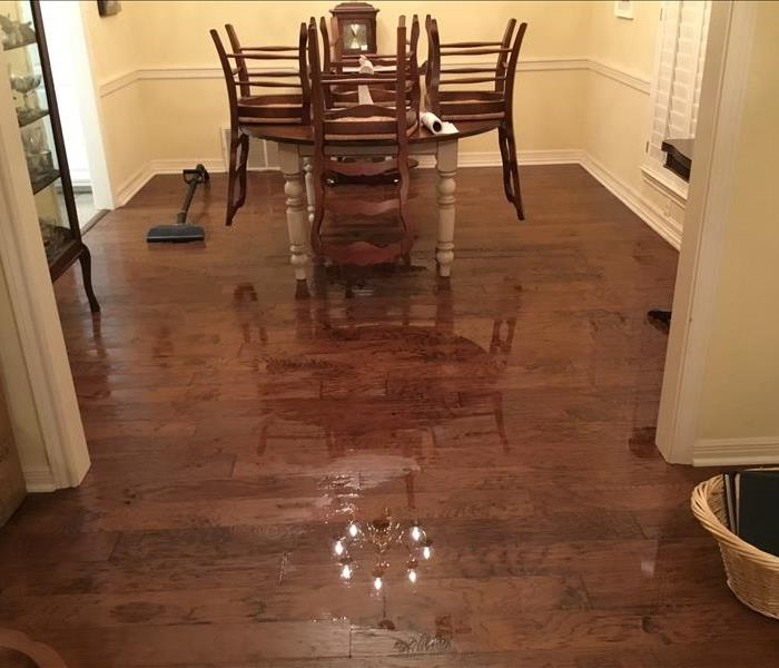 A dining table standing in a puddle in the middle of a wooden floored room